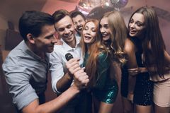 Young people in the club dance and sing. A man in a white shirt is holding a microphone and singing. Stock Photos