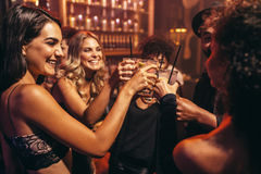 Young people with cocktails at nightclub. Group of young people with cocktails at nightclub. Best friends partying in a pub and toasting drinks Stock Photography