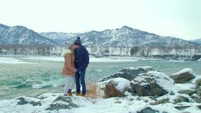 Young people walking in the winter mountains. Young people come to the banks of the river in the winter in the mountains. Slow motion. 4k stock footage