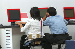 Young people at computer. Two young people are very busy using computers at the airport royalty free stock photography
