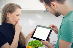 Young people cooking in the kitchen, check top recipes on tablet Stock Image