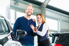 Young people or couple with auto in car dealership Stock Images