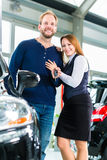 Young people or couple with auto in car dealership Stock Image