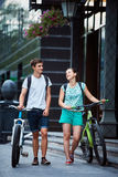 Young people, couple with bicycles on the street Royalty Free Stock Photography