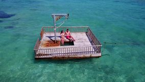 V08586 2 young people couple romantic sunbathing on pontoon with aerial view in beautiful clear aqua blue sea water. 2 young people couple romantic sunbathing on stock footage