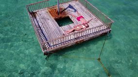 V08567 2 young people couple romantic sunbathing on pontoon with aerial view in beautiful clear aqua blue sea water. 2 young people couple romantic sunbathing on Royalty Free Stock Photos