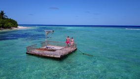 V08550 2 young people couple romantic sunbathing on pontoon with aerial view in beautiful clear aqua blue sea water. 2 young people couple romantic sunbathing on Stock Image