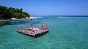 V08551 2 young people couple romantic sunbathing on pontoon with aerial view in beautiful clear aqua blue sea water. 2 young people couple romantic sunbathing on Stock Images