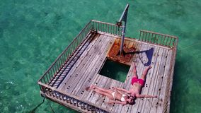 V08564 2 young people couple romantic sunbathing on pontoon with aerial view in beautiful clear aqua blue sea water Royalty Free Stock Image