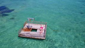 V08556 2 young people couple romantic sunbathing on pontoon with aerial view in beautiful clear aqua blue sea water. 2 young people couple romantic sunbathing on Royalty Free Stock Photo