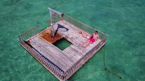 V08590 2 young people couple romantic sunbathing on pontoon with aerial view in beautiful clear aqua blue sea water. 2 young people couple romantic sunbathing on Royalty Free Stock Image