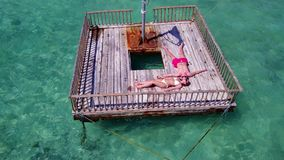 V08566 2 young people couple romantic sunbathing on pontoon with aerial view in beautiful clear aqua blue sea water. 2 young people couple romantic sunbathing on Royalty Free Stock Photography