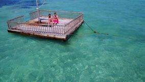 V08580 2 young people couple romantic sunbathing on pontoon with aerial view in beautiful clear aqua blue sea water. 2 young people couple romantic sunbathing on Royalty Free Stock Photography