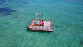 V08585 2 young people couple romantic sunbathing on pontoon with aerial view in beautiful clear aqua blue sea water. 2 young people couple romantic sunbathing on Stock Images