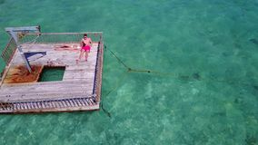 V08594 2 young people couple romantic sunbathing on pontoon with aerial view in beautiful clear aqua blue sea water. 2 young people couple romantic sunbathing on Royalty Free Stock Photography