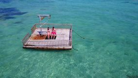 V08584 2 young people couple romantic sunbathing on pontoon with aerial view in beautiful clear aqua blue sea water. 2 young people couple romantic sunbathing on Stock Photography