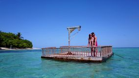 V08573 2 young people couple romantic sunbathing on pontoon with aerial view in beautiful clear aqua blue sea water. 2 young people couple romantic sunbathing on Royalty Free Stock Photography