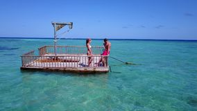 V08575 2 young people couple romantic sunbathing on pontoon with aerial view in beautiful clear aqua blue sea water. 2 young people couple romantic sunbathing on Royalty Free Stock Photo