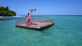 V08577 2 young people couple romantic sunbathing on pontoon with aerial view in beautiful clear aqua blue sea water. 2 young people couple romantic sunbathing on Stock Images