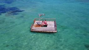 V08587 2 young people couple romantic sunbathing on pontoon with aerial view in beautiful clear aqua blue sea water. 2 young people couple romantic sunbathing on Royalty Free Stock Photos