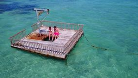 V08583 2 young people couple romantic sunbathing on pontoon with aerial view in beautiful clear aqua blue sea water. 2 young people couple romantic sunbathing on Stock Images