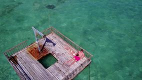 V08591 2 young people couple romantic sunbathing on pontoon with aerial view in beautiful clear aqua blue sea water. 2 young people couple romantic sunbathing on Royalty Free Stock Photos