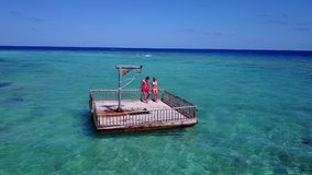 V08599 2 young people couple romantic sunbathing on pontoon with aerial view in beautiful clear aqua blue sea water. 2 young people couple romantic sunbathing on Stock Photo