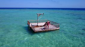 V08571 2 young people couple romantic sunbathing on pontoon with aerial view in beautiful clear aqua blue sea water. 2 young people couple romantic sunbathing on Royalty Free Stock Photo