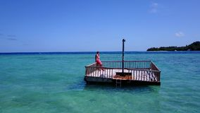 V08553 2 young people couple romantic sunbathing on pontoon with aerial view in beautiful clear aqua blue sea water. 2 young people couple romantic sunbathing on Stock Photos