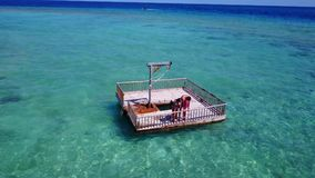 V08560 2 young people couple romantic sunbathing on pontoon with aerial view in beautiful clear aqua blue sea water. 2 young people couple romantic sunbathing on Stock Photo