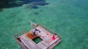 V08589 2 young people couple romantic sunbathing on pontoon with aerial view in beautiful clear aqua blue sea water. 2 young people couple romantic sunbathing on Royalty Free Stock Photography