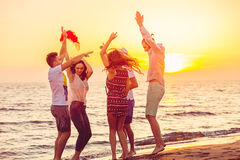 Young People Dancing On Beach at Sunset royalty free stock images