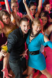 Young people dancing in club or disco, men and women Stock Images