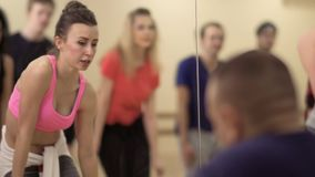 Young people are dancing in front of the mirror