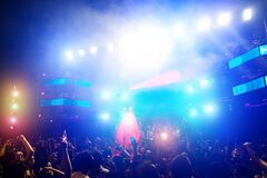 Young people dancing and having fun in summer festival party outdoor - Crowd with hands up and smarphones celebrating fest concert