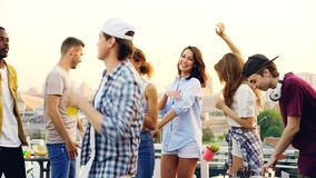 Young people are dancing and laughing while male DJ is working with equipment at rooftop party on summer day. Entertainment, modern youth and music concept stock footage