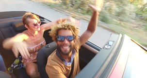 Young people dancing to party music in convertible. Young people dancing to party music while driving in convertible stock footage