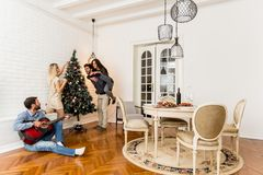 Young people decorate fir-tree for holidays of Christmas and New Stock Images