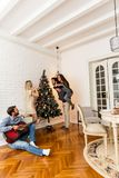 Young people decorate fir-tree for holidays of Christmas and New Royalty Free Stock Image