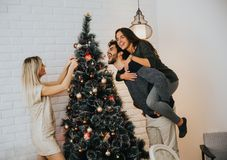Young people decorate fir-tree for holidays of Christmas and New Stock Image