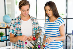 Young people decorating christmas tree in office Royalty Free Stock Photography