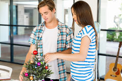 Young people decorating christmas tree in office Stock Photo