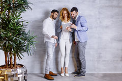 Young people with digital tablet by the grey wall Stock Image