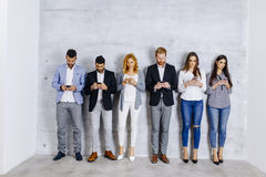 Young people with digital tablet by the wall Royalty Free Stock Photography