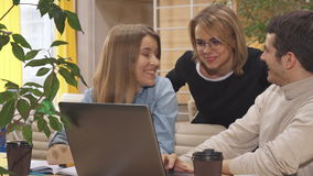 Young people discuss some project on laptop. Young caucasian people discussing some project on laptop at the working hub. Two attractive women and one man stock footage