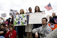 Young people display signs at tea party rally. Royalty Free Stock Photo