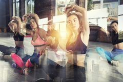 Young people do stretching at the gym. Double exposure. Class of people do stretching at the gym. Double exposure stock images