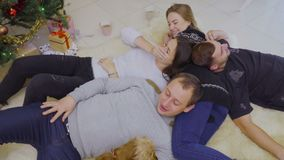 Young people and dog lays on floor near Christmas tree. Four young people lays on floor on carpet and relax. People celebrates Christmas and spend their leisure stock footage