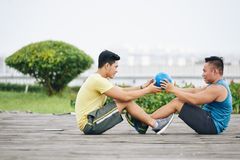Abs workout. Young people doing abs exercise with ball stock photo