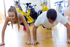 Young people doing exercise on the floor in the gym. Stock Photos